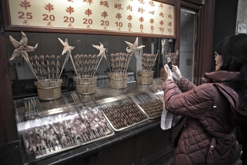 Una mujer china haciendo una foto a un pincho moruno de escorpiones en Pekin