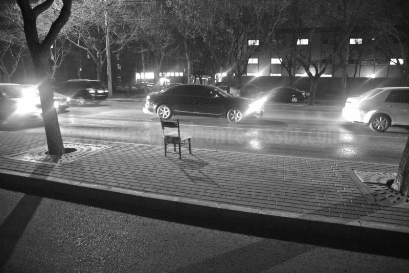 Una silla solitaria esperando a su dueno al pie de una calle de Pekín